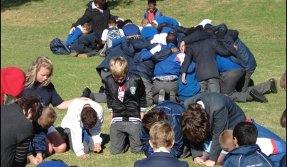 Learners, teachers praying together at PE schools