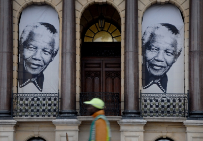 A pedestrian walks beneath two giant portraits outside the City Hall in Cape Town, South Africa, Monday, June 24, 2013 where on the balcony former South Africa president Nelson Mandela made his first public speech after being released from 27 years of imprisonment. (PHOTO: AP)