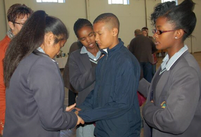 Fountain of Life Christian School students pray with a learner at Alexandria Christian Academy.