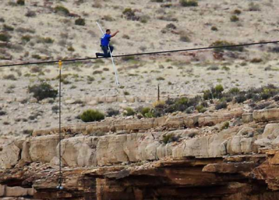 Daredevil Nik Wallenda gives a thumbs-up sign as he nears the end, after walking on a two-inch (5-cm) diameter steel cable rigged 1,400 feet (426.7 metres) across more than a quarter-mile deep remote section of the Grand Canyon near Little Colorado River, Arizona June 23, 2013. Read more at http://www.christianpost.com/news/nik-wallenda-constantly-prayed-to-jesus-during-successful-grand-canyon-tightrope-walk-98616/#9j1vZxfvm5YlHJA2.99