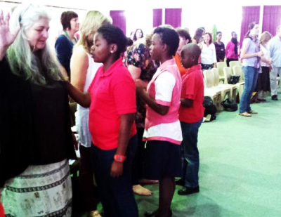 Oasis Christian Academy students praying for people at prophetic conference.