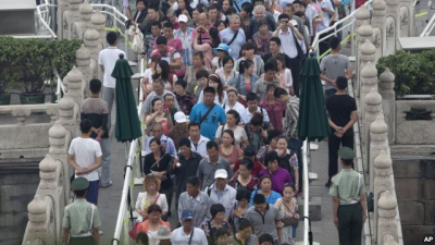 Visitors walk past the plain clothes policemen and paramilitary policemen as they enter Tiananmen Gate in Beijing, June 4, 2013.