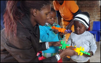 Mission Aviation Fellowship volunteer Chimwemwe Calawe shows children how to use educational toys.