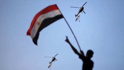 Egyptian military helicopters trailing national flags circle over Tahrir Square during a protest demanding that Egyptian President Mohamed Morsi resign in Cairo. The military says Morsi and the opposition must resolve the crisis or it will impose its 'road plan for peace.' (Suhaib Salem/Reuters)