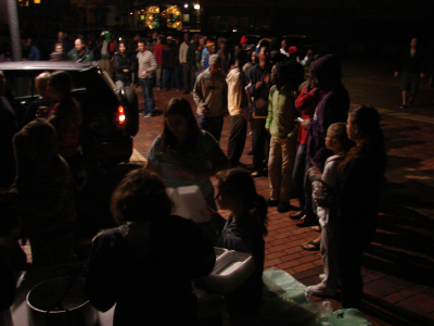 Homeless people queue for supper at a 'city feed'