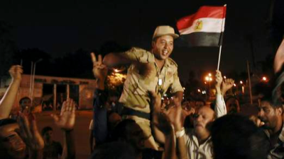 A soldier cheers with anti-Morsi protesters.