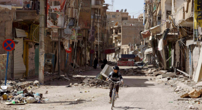 A boy rides his bicycle past damaged buildings in Deir al-Zor, Syria, April 3. (CNS photo/ Khalil Ashawi, Reuters).
