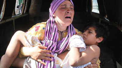 "A Syrian woman carries her injured son, who was shot by the border guards as the pair crossed a river from Syria to Lebanon. UN chief Ban Ki-moon declared ""civil war"" in Syria. (PHOTO: AP)"