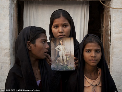 Worried: The daughters of Asia Bibi pose with an image of their mother. (PHOTO: LATIF/Reuters/Corbis)