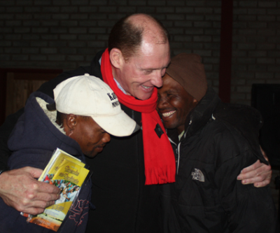 Evangelis Johnny Louw juig saam twee manne wat hulle harte by Juriesbaken op 7 Augustus 2013 vir die Here gegee het.