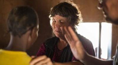 Nurse Lenie Coetzer prays for a woman during a medical outreach to Nsovwe village. (PHOTOl Brad Livengood).