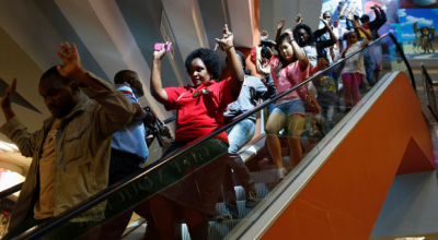 Civilians escape an area at the Westgate shopping centre in Nairobi on Saturday, where al-Shabab killed at least 62 people. (PHOTO: Reuters/Siegfried Modola ).