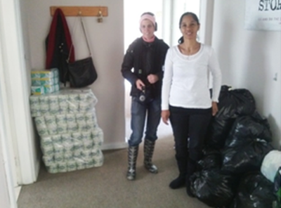 Seen in the photograph on the left standing next to piles of black bags full of clothing and nearly 200 toilet rolls that were donated are Adele Liebich and Faye Ansley.