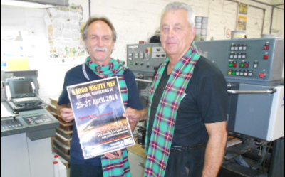 Alan Taylor of Bukani Print with one of the KMMC 2014 publicitiy posters. KMMC Committee Member, Lance Walton (right), presented Taylor with a  Mighty Men tartan scarf in recognition of his support of the KMMC marketing drive.