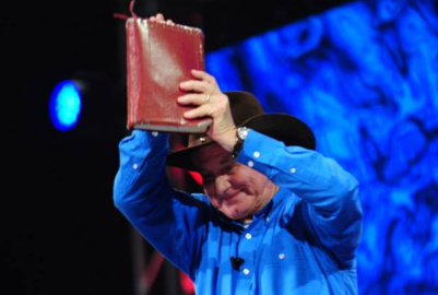 Angus Buchan holds his 'agricultural manual' (Bible) high at the Mighty Men USA at Bridgestone Stadium in Nashville, Tennessee, on Sunday.