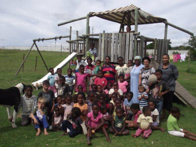 Some of the children and volunteers in the outdoor play area at JJH.