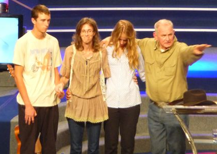 Angus Buchan prays with Yolande Korkie (2nd from left), wife of Al-Qaeda hostage Pierre Korkie,  and her 16-year-old son and 14-year-old daughter in the CRC auditorium in Bloemfontein today. (PICTURE: Lyzette Hoffman)