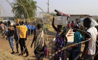 Displaced people walk past razor wire at Tomping camp, where some 15,000 displaced people who fled their homes are sheltered by the United Nations, near Juba January 7, 2014. (PHOTO: REUTERS/James Akena),