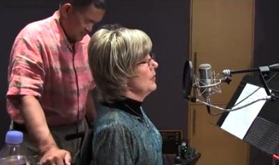 "Joni Eareckson Tada prays before singing ""Alone But Not Alone'."