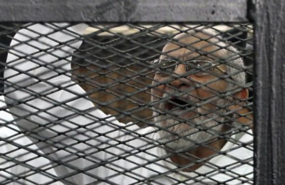 Muslim Brotherhood leader Mohammed Badie shouts slogans from the defendant's cage during his trial with other leaders of the Brotherhood in a courtroom in Cairo December 11, 2013. (PHOTO: Reuters/Stringer)