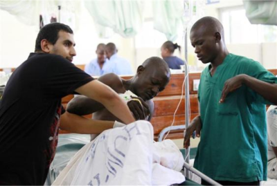A medic attends to an injured man, a victim from an attack on a church by gunmen, at the Coast General Hospital in Kenya's coastal town of Mombasa, March 23, 2014.  (PHOTO: Reuters/Joseph Okanga)