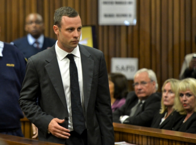 Oscar Pistorius is watched by June Steenkamp, 2nd right, the mother of Reeva Steenkamp, as he arrives for his trial at the high court in Pretoria, South Africa, Monday, March 3, 2014. Pistorius is charged with murder with premeditation in the shooting death of girlfriend Reeva Steenkamp in the pre-dawn hours of Valentine's Day 2013.