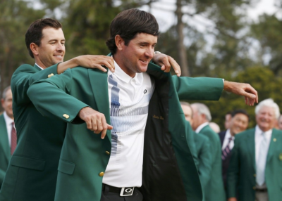 Masters winner Bubba Watson is presented with his green jacket by 2013 winner Adam Scott (L) after winning the Masters golf tournament at the Augusta National Golf Club in Augusta, Georgia, April 13, 2014.