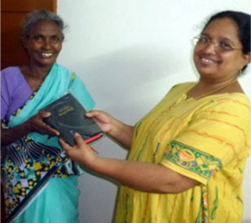 Nagamma (Maria) receives Bible from Mercy Ciniraj (right),
