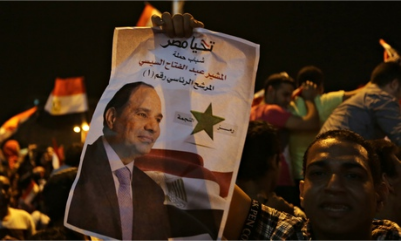 A supporter holds up a poster of Egypt's former army chief Abdel Fatah al-Sisi as he celebrates in Tahrir Square in Cairo. Photograph: Amr Abdallah Dalsh/Reuters