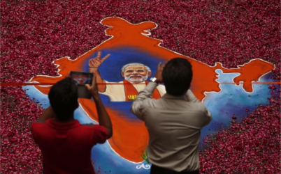 Indians take photographs of a portrait of Bharatiya Janata Party (BJP) leader Narendra Modi, made with colored powder and surrounded by rose petals, at the party office in Gandhinagar, in the western Indian state of Gujarat, Friday, May 16, 2014. Modi will be India's next prime minister, winning the most decisive election victory the country has seen in more than a quarter century and sweeping the long-dominant Congress party from power, partial results showed Friday. (PHOTO: AP /Saurabh Das)