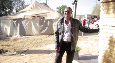 Pastor Sipho in front of the old tent which has been serving as church and community centre for nearly 20 years.