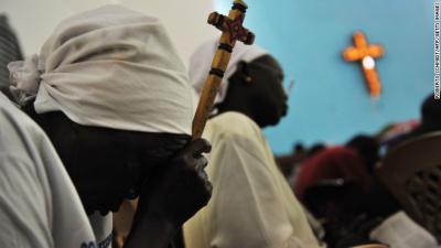 A Sudanese woman holds a cross as she prays. (PHOTO: CNN)