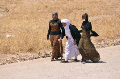 Displaced families from the minority Yazidi sect, fleeing the violence, walk on the outskirts of Sinjar, west of Mosul.