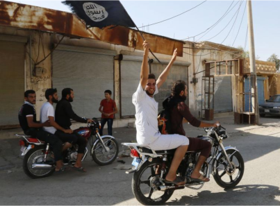 A resident of Tabqa city touring the streets on a motorcycle waves an Islamist flag in celebration after Islamic State militants took over Tabqa air base, in nearby Raqqa city August 24, 2014. (PHOTO: Stringer/Reuters).