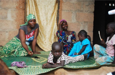 A woman talks about her escape from violence after Boko Haram insurgents attacked her community weeks ago, while sitting near others at the internally displaced persons (IDP) camp at Wurojuli, Gombe State September 2, 2014. REUTERS/Samuel Ini