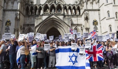 People hold placards and Israeli and Union flags outside the Royal Courts of Justice as Jewish groups rally in London on August 31 (PHOTO: AFP).
