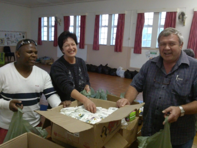 Joel Stuurman, Lizette Rheeder and Andrew Johnson share a joke whilst packing the toiletry bags for the guests.