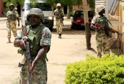 In this photo dated 6 June 2013, soldiers stand guard at the offices of the state-run Nigerian Television Authority in Maiduguri, Nigeria. The radical group Boko Haram once attacked only government institutions and security forces, but now increasingly targets civilians.
