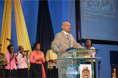 "(PHOTO: FACEBOOK/KEVIN ""MINISTER K"" HARRIS) Dave Burrows (podium), the new senior pastor of Myles Munroe's Bahamas Faith Ministries."