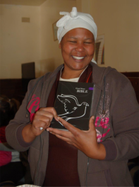 A happy lady with her first ever Bible which was given to her during the Bag Angels' first shelter visit.