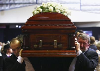 Gregory (R) and Jason Hughes, the father and brother respectively of Australian cricketer Phillip Hughes, carry his casket past mourners after his funeral service, on December 3, 2014.(PHOTO: Reuters).