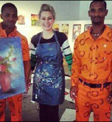Lisa Crumpton poses with two offenders on the last day of the art workshop.