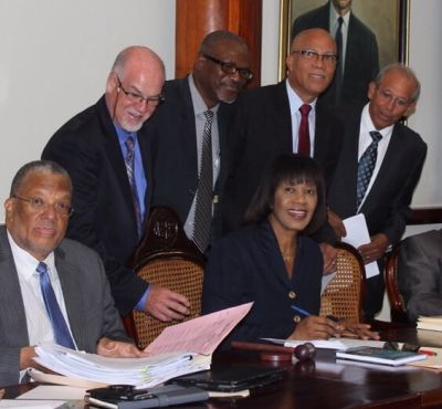 Jamaican Prime Minister Honourable Mrs Portia Simpson-Miller, signs the Unashamedly Ethical (UE) pledge form. UE founder, Graham Power (second from left) looks on together with Jamaican leaders.