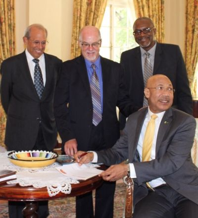 The Governor General of Jamaica,  His Excellency Sir Patrick Allen, signs the UE pledge. He is witnessed by (from left) Robert Levy, Graham Power and Oral McCook.