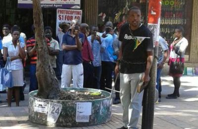 Pastor chains himself to pole in anti-Mugabe protest