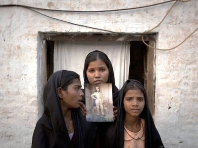 the-daughters-of-asia-bibi-with-an-image-of-their-mother-standing-outside-their-residence-in-sheikhupura-on-november-13-2010